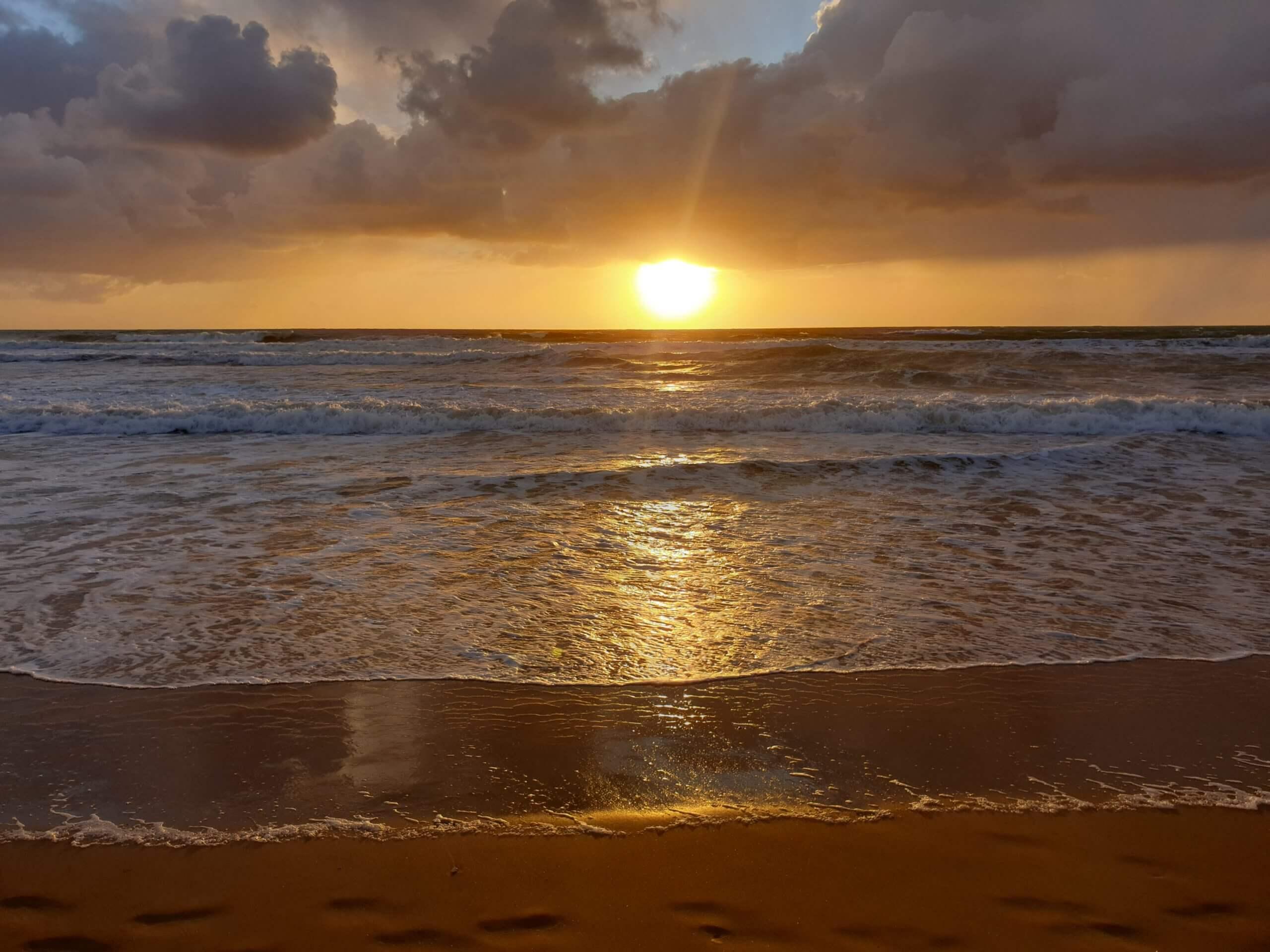 Bord de mer avec couché de soleil au loin (soleil orangé)